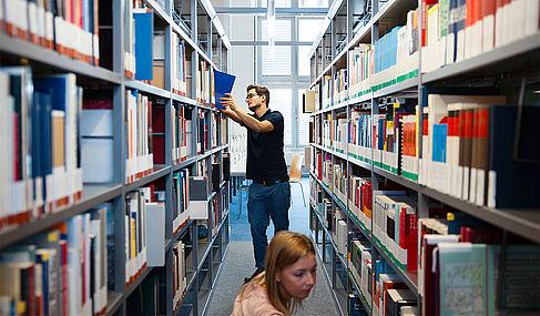 Eine Studentin und ein Student in der Bibliothek am Bücherregal © HTW Berlin