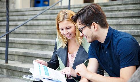 Eine Studentin und ein Student sitzen auf einer Treppe und blättern in einer Broschüre © HTW Berlin
