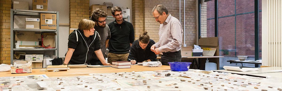 Studierende und Professor an einem Tisch voller Exponate