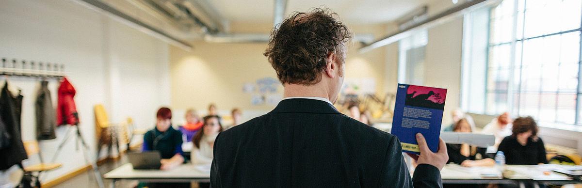 Professor mit einem Buch in der Hand lehrt vor Studierenden